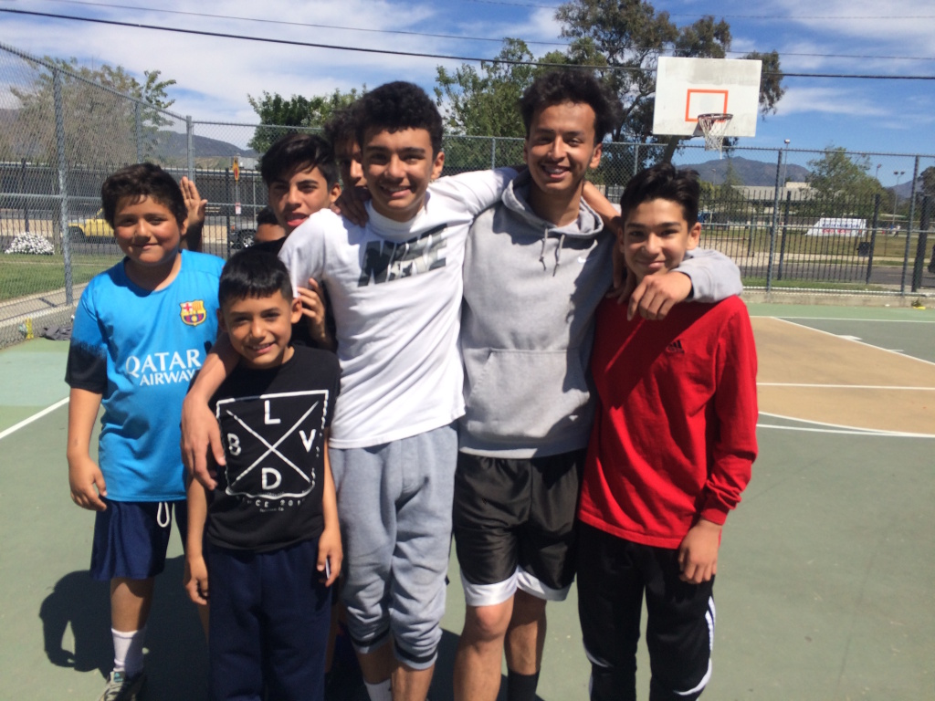 Jaime Zombrano, 17, second from right, takes a break from playing basketball with his friends at San Fernando Gardens housing in Pacoima. The neighborhood has gotten much safer from when he was a kid, though a deadly shooting of a teen in October 2015 on the block brought back bad memories, he said.
