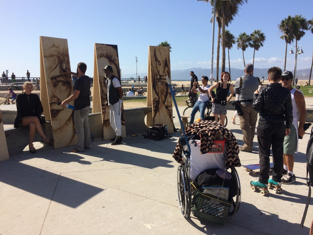 A crowd gathers on the Venice Boardwalk to watch Aronson paint. He regularly works at art walks and other live outdoor events around Los Angeles.