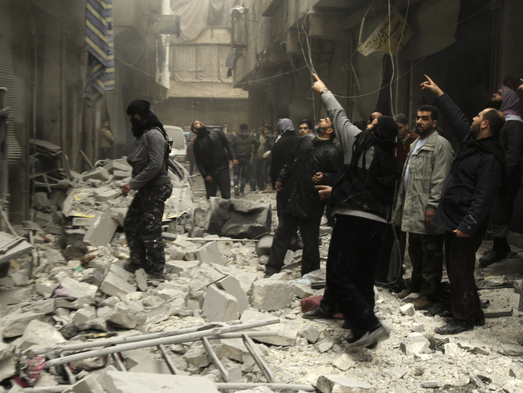 Syrian look up after an apparent airstrike by forces loyal to President Bashar Assad in Aleppo, Syria, on Monday. A new report, released Monday, alleges