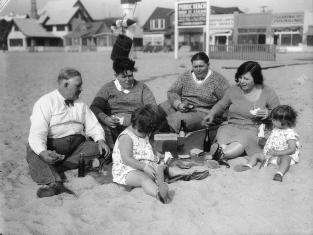 LAPL ARCHIVE CAPTION, UNDATED PHOTO: A family of six enjoys a picnic at Venice beach. They sit on the sand and enjoy sandwiches and soda pop. The two young men sitting in the middle wear similar sweaters, shirts and bow ties, while the two little girls in the front wear matching white print dresses. A sign posted on the beach reads: