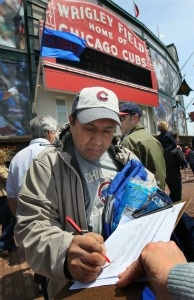 Chicago Cubs fan Tony Medina signs a petition urging the team to move their spring training camp out of Arizona.