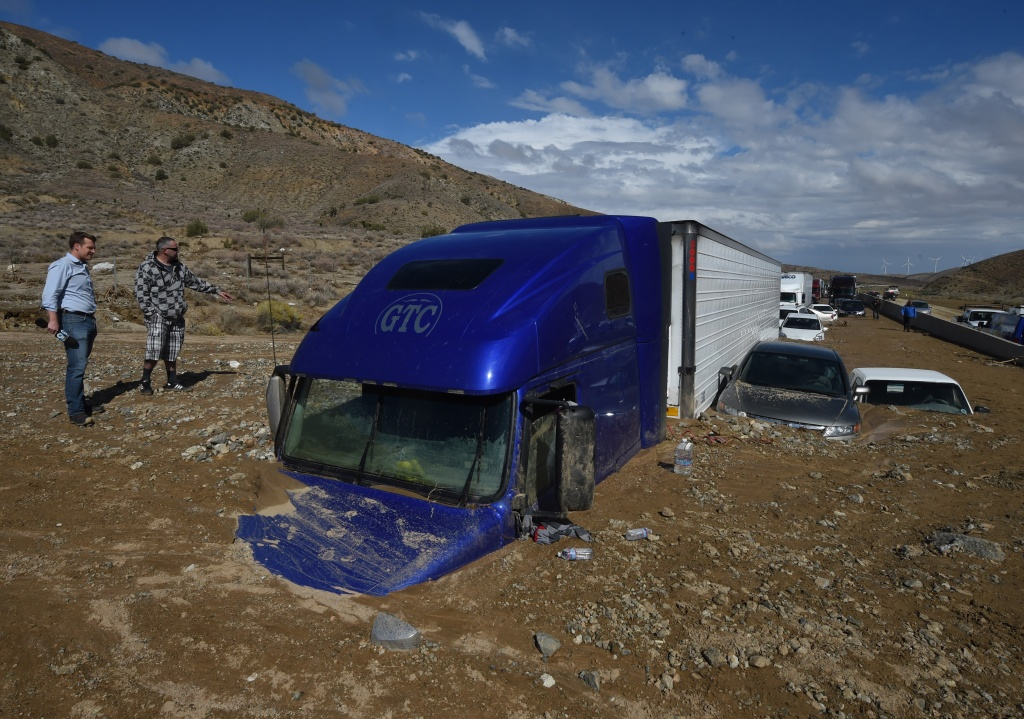 Reporters look vehicles stuck on a road after being trapped by a mudslide on California Highway 58 in Mojave, California on Oct. 16, 2015, after torrential rains swamped the area and forced drivers and passengers to flee on foot.  75 tractor-trailers and two tour buses were among the 115 vehicles caught up in the disaster.