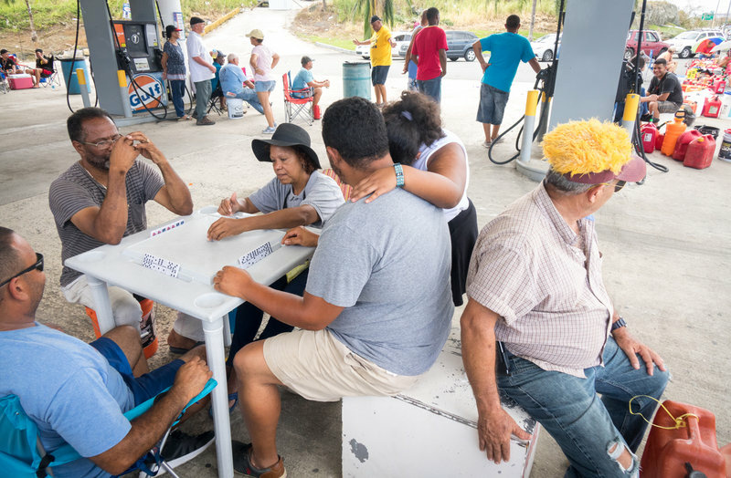 People play dominoes while waiting in line for gas. Limited availability of gas has been a problem across Puerto Rico ever since Hurricane Maria hit last week.