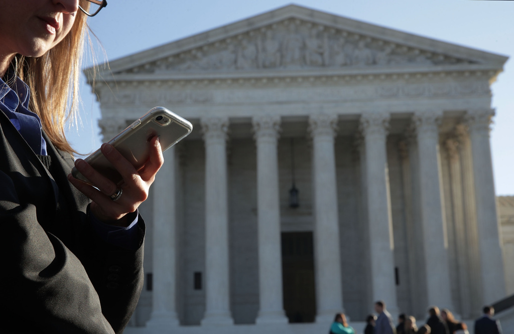 A woman checks her cell phone as she waits in line to enter the U.S. Supreme Court to view a hearing November 29, 2017 in Washington, DC. The Supreme Court is scheduled to hear Carpenter v. United States today on whether prosecutors violated the Fourth Amendment by collecting a criminal suspect's cellphone location and movement data without a warrant.