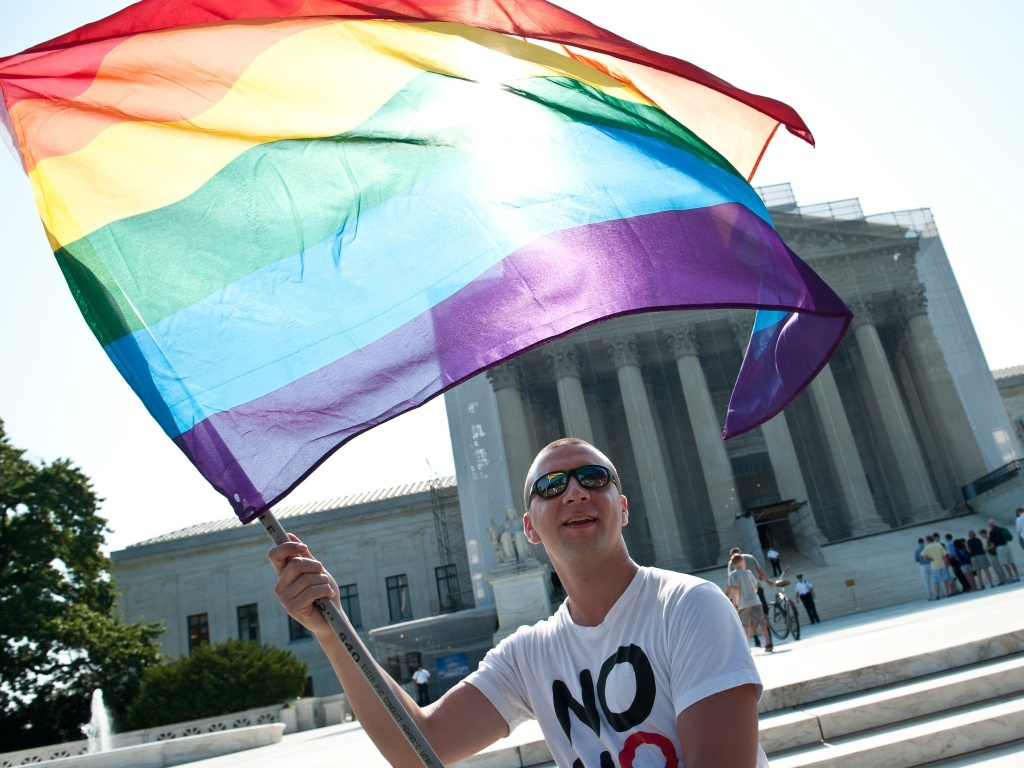 File photo: A gay rights activist waves a rainbow flag in front of the U.S. Supreme Court in June, a day before the ruling on the Defense of Marriage Act.