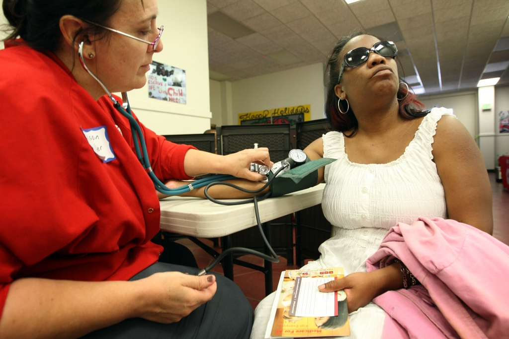 Nurse Allison Miller (L) checks the blood pressure of Keri Anderson as nurses and physicians give free basic health screenings and call attention to what they say is the ongoing healthcare emergency despite the decision of the U.S. Supreme Court to uphold the Affordable Care Act, on July 10, 2012 in Los Angeles, California.