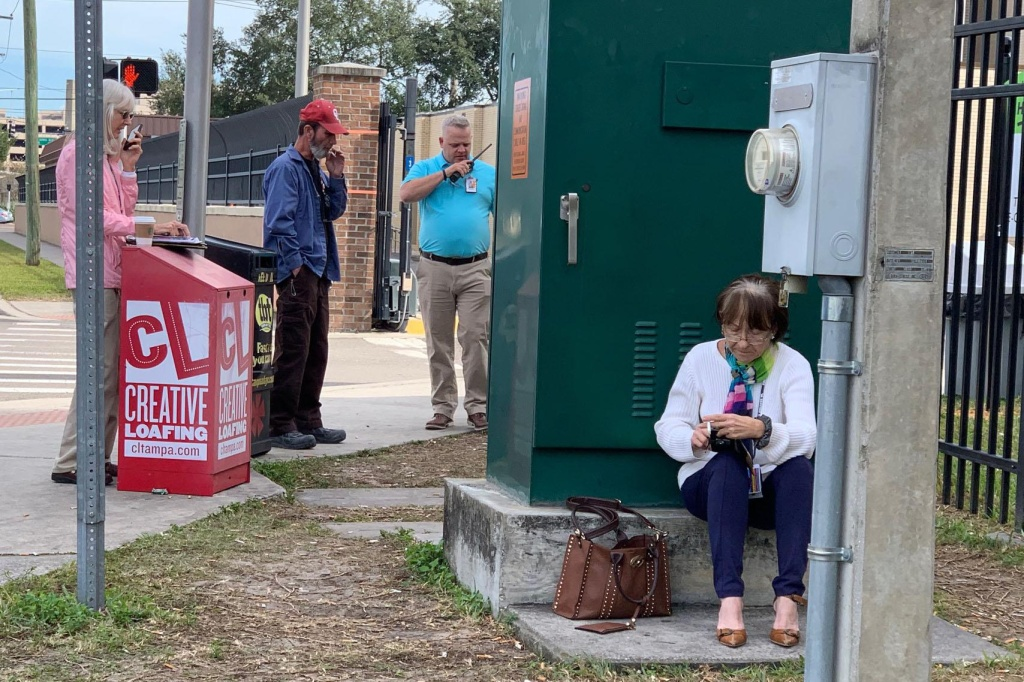 Smokers congregate outside the fence of the VA hospital in Tampa.