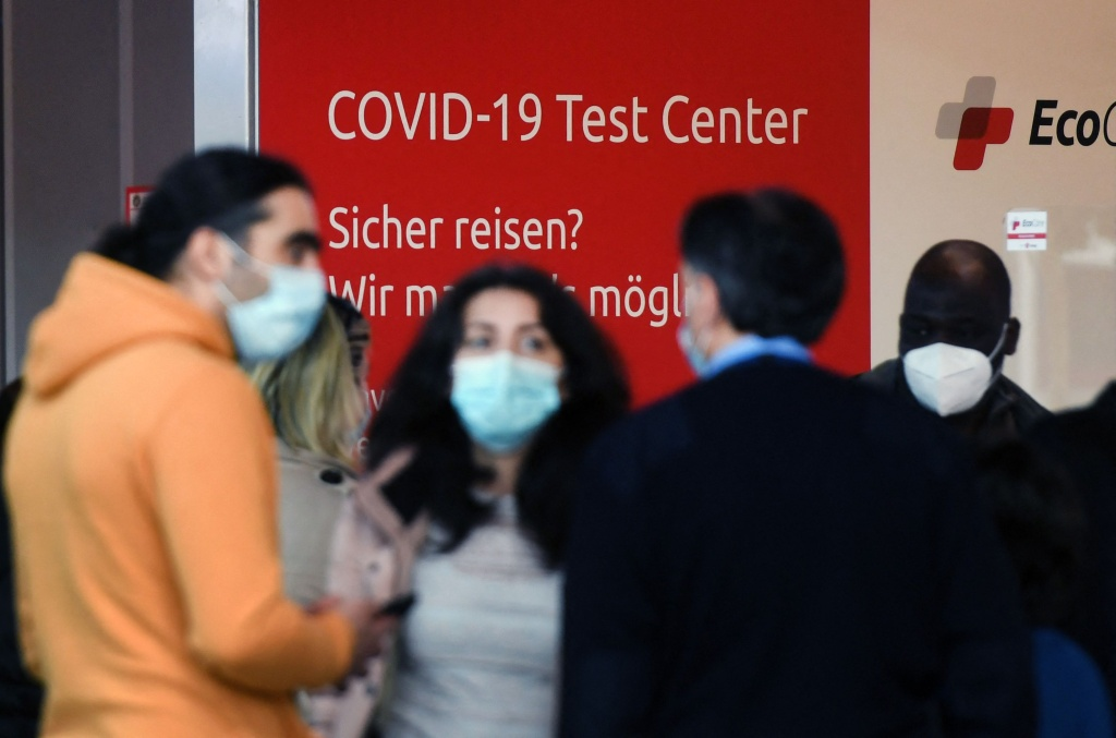 Passengers queue at a Covid-19 test center at the departure level at the Duesseldorf airport, western Germany on March 26, 2021.