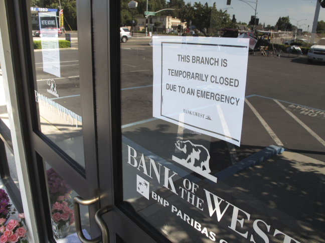 This Wednesday July 16, 2014 image provided by the Stockton Police Department shows a closed sign on a Stockton, Calif. bank after a robbery. Three bank robbers took three women hostage as they made a getaway and waged a high-speed gunbattle with police that left three people dead and cars and homes riddled with bullets, authorities said.