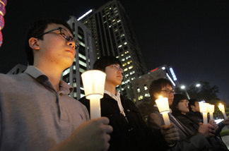 South Koreans take a moment of silence for South Korean marines killed in a North Korean bombardment during a rally against North Korea's attack onto South Korean island, in Seoul, South Korea, Tuesday, Nov. 23, 2010. North Korea shot dozens of rounds of artillery onto a populated South Korean island near their disputed western border Tuesday, military officials said, setting buildings on fire and prompting South Korea to return fire and scramble fighter jets.