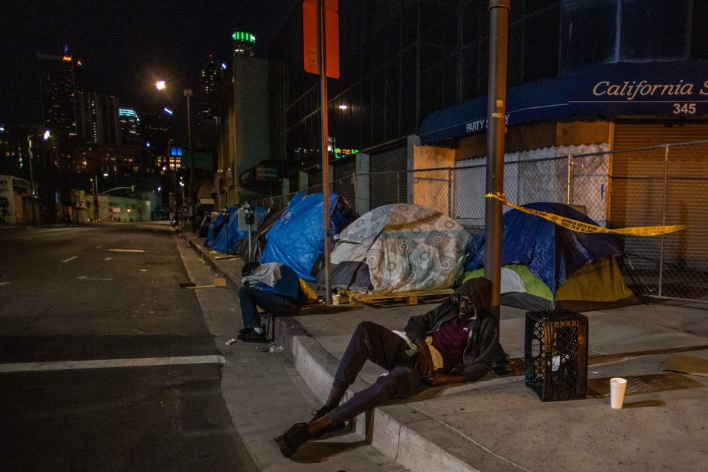 Homeless men are seen sleeping on the street of Skid Row during the COVID-19, Coronavirus pandemic in Los Angeles, California.