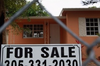 A for sale sign stands in front of a home in Miami, Florida. A measure of Americans who signed contracts to buy homes increased last month to its highest level in two and a half years, the latest sign of improvement in the once-battered housing market.