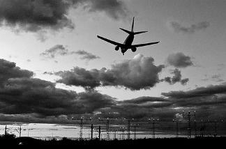 An airplane lands beneath darkened skies.