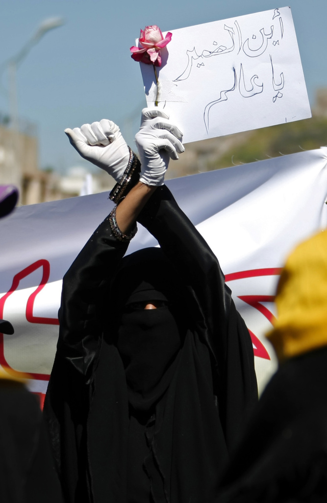 A fully-veiled pro-reform protester holds a sign which reads in Arabic
