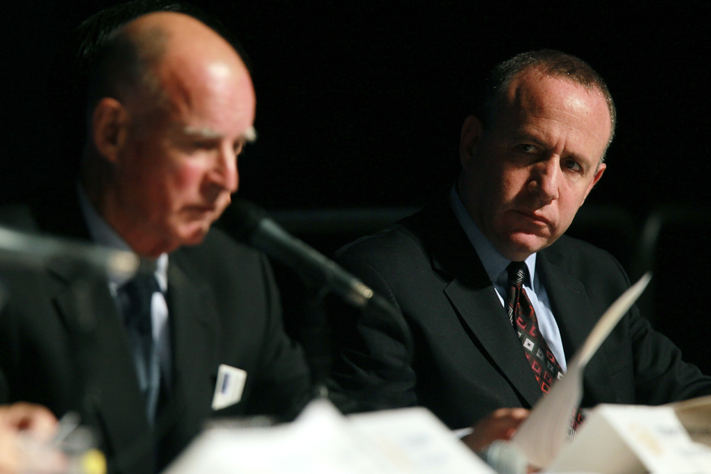 California state senate president Darrell Steinberg (R) looks on as California governor-elect Jerry Brown speaks during a briefing.