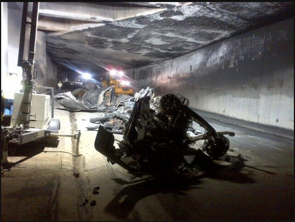 File: The inside of the tunnel shows damage to the structure and what's left of the burned out gasoline tanker truck.