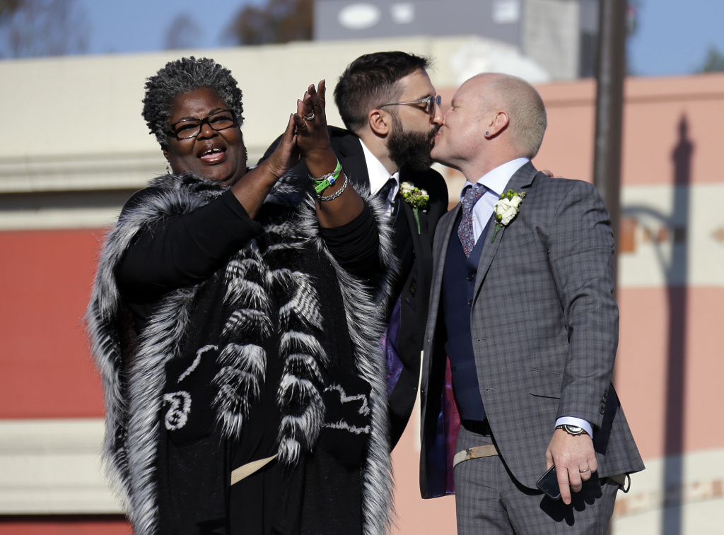 Aubrey Loots, right, and Danny Leclair, the first gay couple to be married aboard a float in the Tournament of Roses, kiss after being wed by the Rev. Alfreda Lanoix of the Unity Fellowship Church of Christ, left, aboard the AIDS Healthcare Foundation float in the 125th Rose Parade in Pasadena, Calif., Wednesday, Jan. 1, 2014. (AP Photo/Reed Saxon)