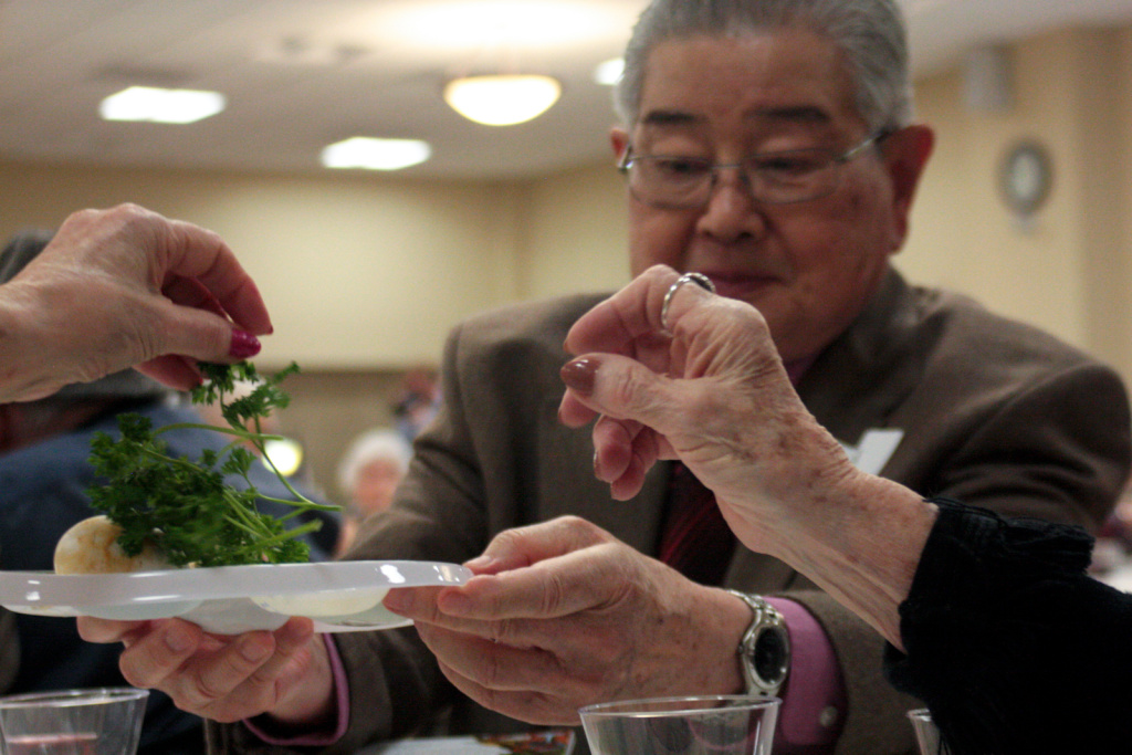 Paul Fujimoto, a Keiro resident, passes the parsley to women from the Los Angeles Jewish Home who teach him to dip it in salt water.