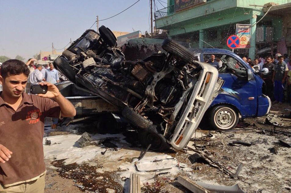 Iraqis gather at the scene of an explosion in Aziziyah, south of the Iraqi capital Baghdad on June 16, 2013. Seven vehicles rigged with explosives went off in five cities south of Baghdad during the morning rush hour, leaving 56 people wounded and 20 dead in primarily Shiite Muslim areas of Iraq.