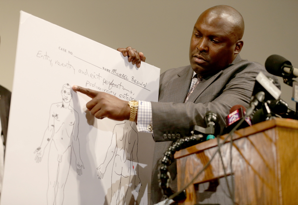 Family attorney for Michael Brown, Daryl Parks, points to an autopsy diagram showing where the gun shots hit Michael Brown during a press conference at  the Greater St. Marks Family Church on August 18, 2014 in Ferguson, Missouri. Unarmed teenager Michael Brown was shot and killed by a Ferguson police officer on August 9th.