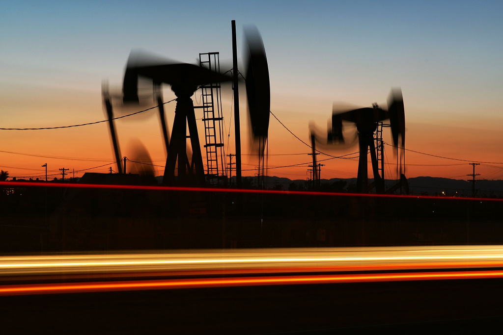 Car lights are seen streaking past an oil rig extracting petroleum.  (Photo by David McNew/Getty Images)