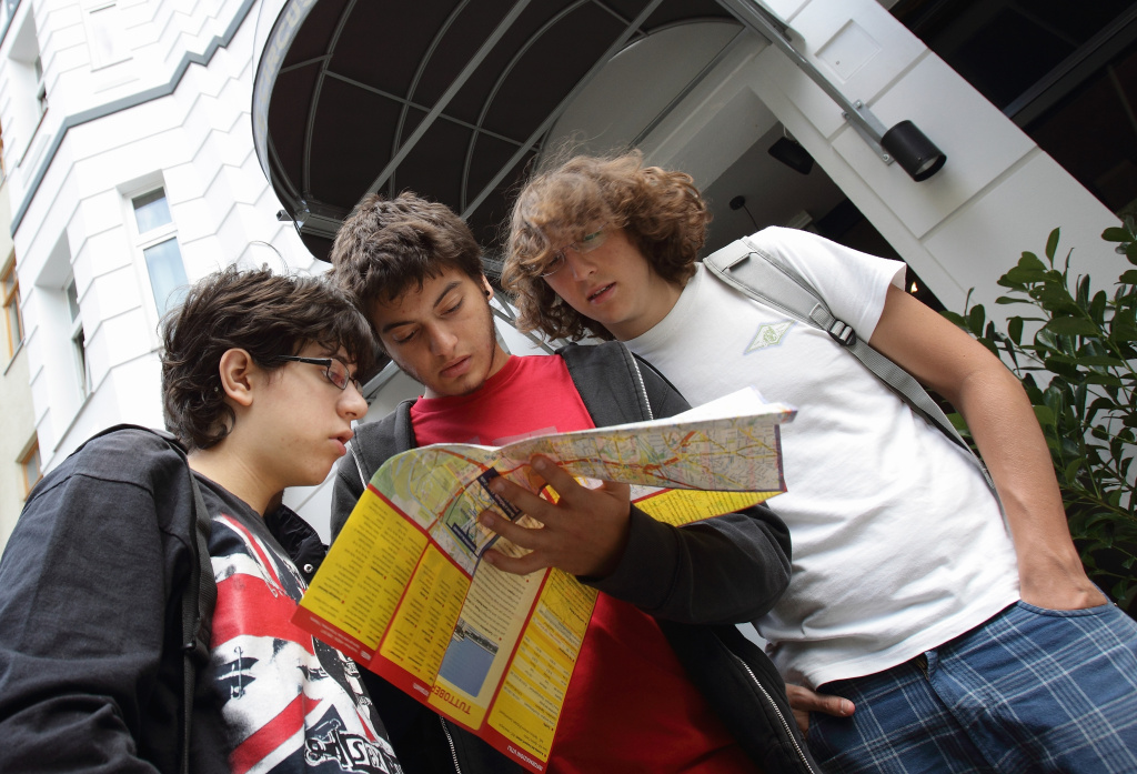 Youth backpackers of Spain study a map outside the Circus hostel Berlin on July 19, 2010 in Berlin, Germany. Millions of youth people taking a gap year between high school and college to see the world. Backpacking is the cheapest way to travel the world.