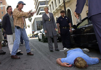 Director Patrick Norris (C) prepares to film a scene as Assistant Director Brad Gross (L), actors and crew look on, on the set of Paramount Pictures' television series 'The Division' in downtown Los Angeles, CA.