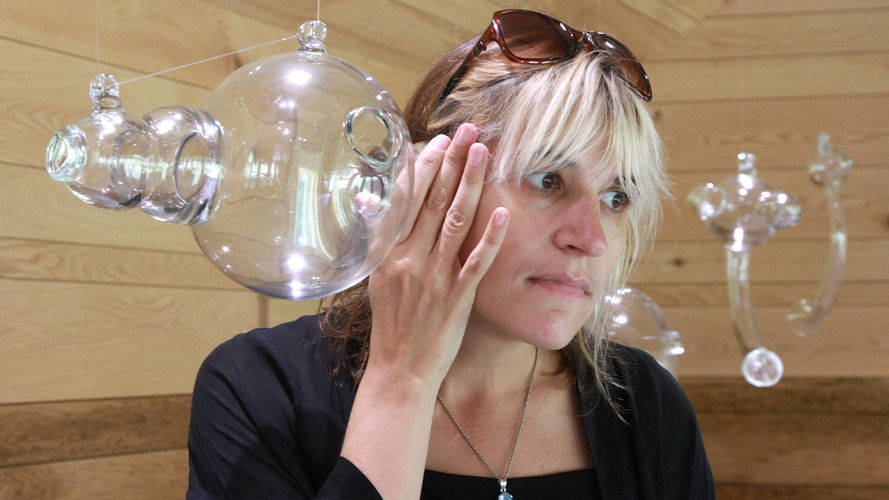 Artist Andrea Polli listens to modified bat sounds through a glass vessel inspired by Helmholtz resonators at the Marsh-Billings-Rockefeller National Historic Park in Woodstock, Vt.