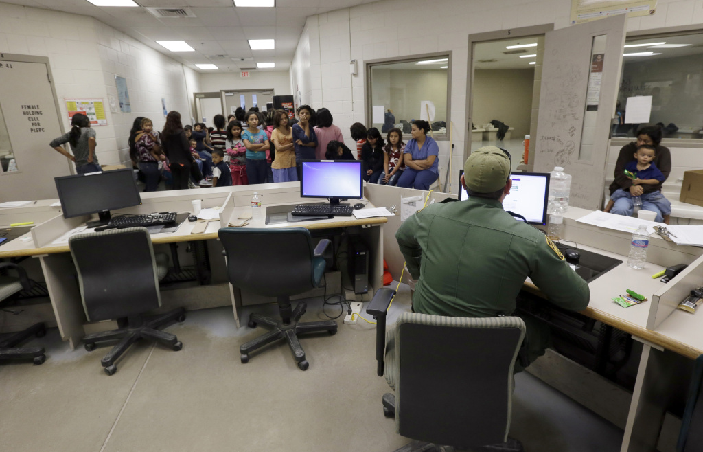 FILE: In this June 18, 2014 photo, U.S. Customs and Border Protection agents work at a processing facility in Brownsville, Texas. Immigration courts backlogged by years of staffing shortages and tougher enforcement have been challenged by Central Americans arriving on the U.S. border fleeing violence back home.