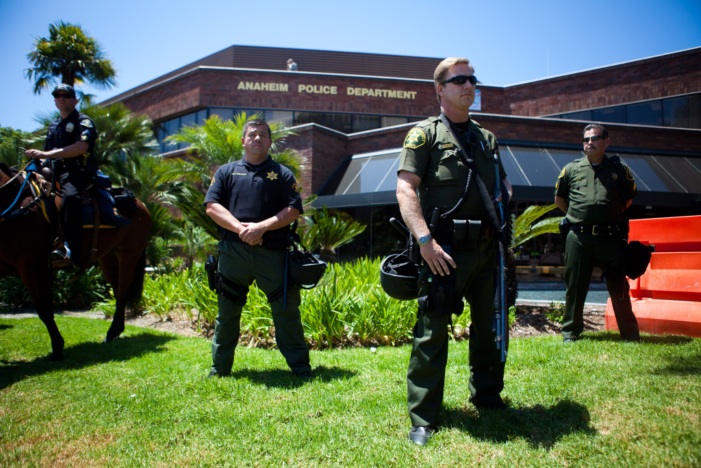 ANAHEIM, CA - JULY 29:  A line of police officers guard the Anaheim Police Department before a protest to show outrage for the several recent officer-involved shootings on July 29, 2012 in Anaheim, California. For the past week, protesters have clashed with police resulting in both property damage and many arrests.  (Photo by Jonathan Gibby/Getty Images)