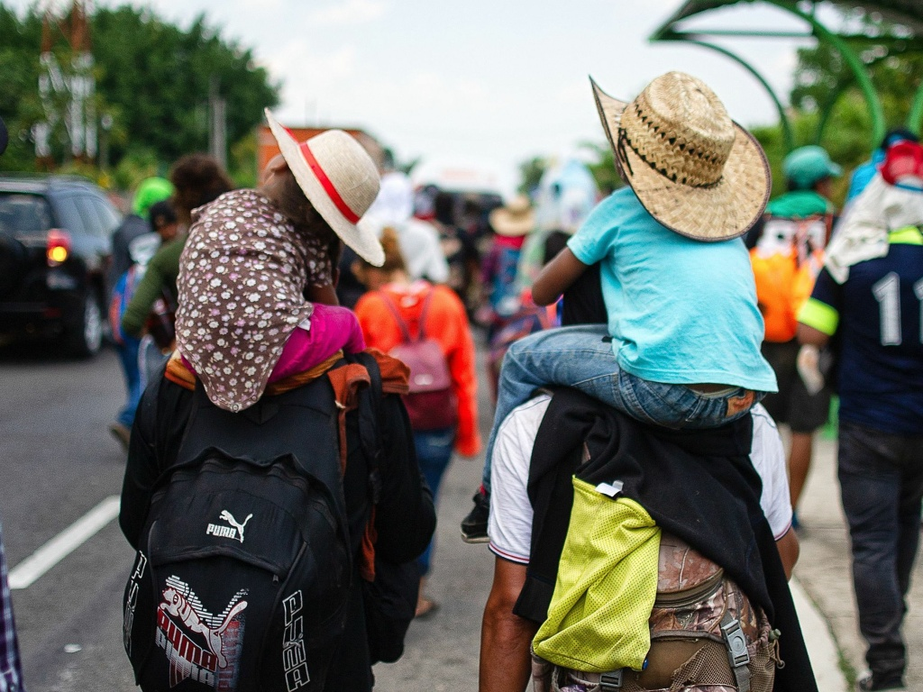 Children are carried on the shoulders of Central American migrants heading to the U.S. along the road between Metapa and Tapachula, Mexico, on April 12. President Trump has called for measures to close what he calls the asylum
