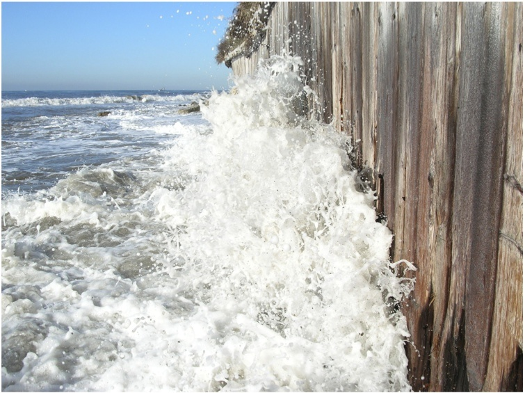A wave hits a timber seawall on the Gaviota Coast in Santa Barbara.