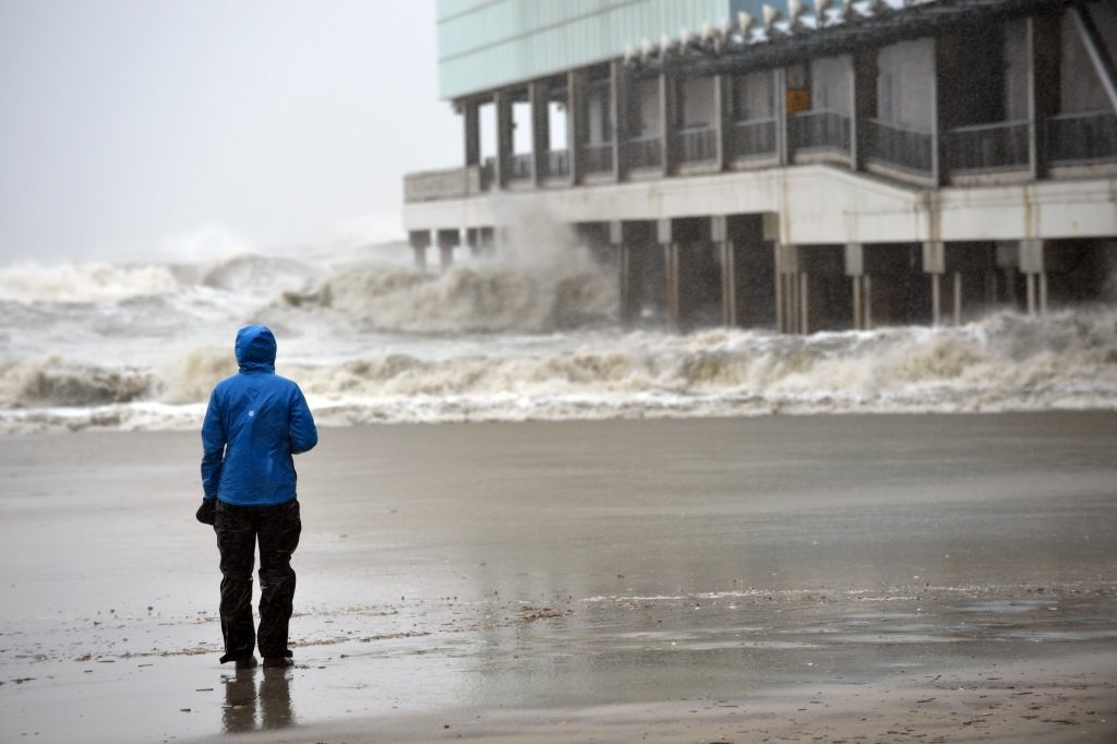 A television reporter watches waves hit a pier before the arrival of Hurricane Sandy October 29, 2012 just off the Boardwalk in Atlantic City, New Jersey. Much of the eastern United States was in lockdown mode October 29, 2012 awaiting the arrival of a hurricane dubbed 'Frankenstorm' that threatened to wreak havoc on the area with storm surges, driving rain and devastating winds.