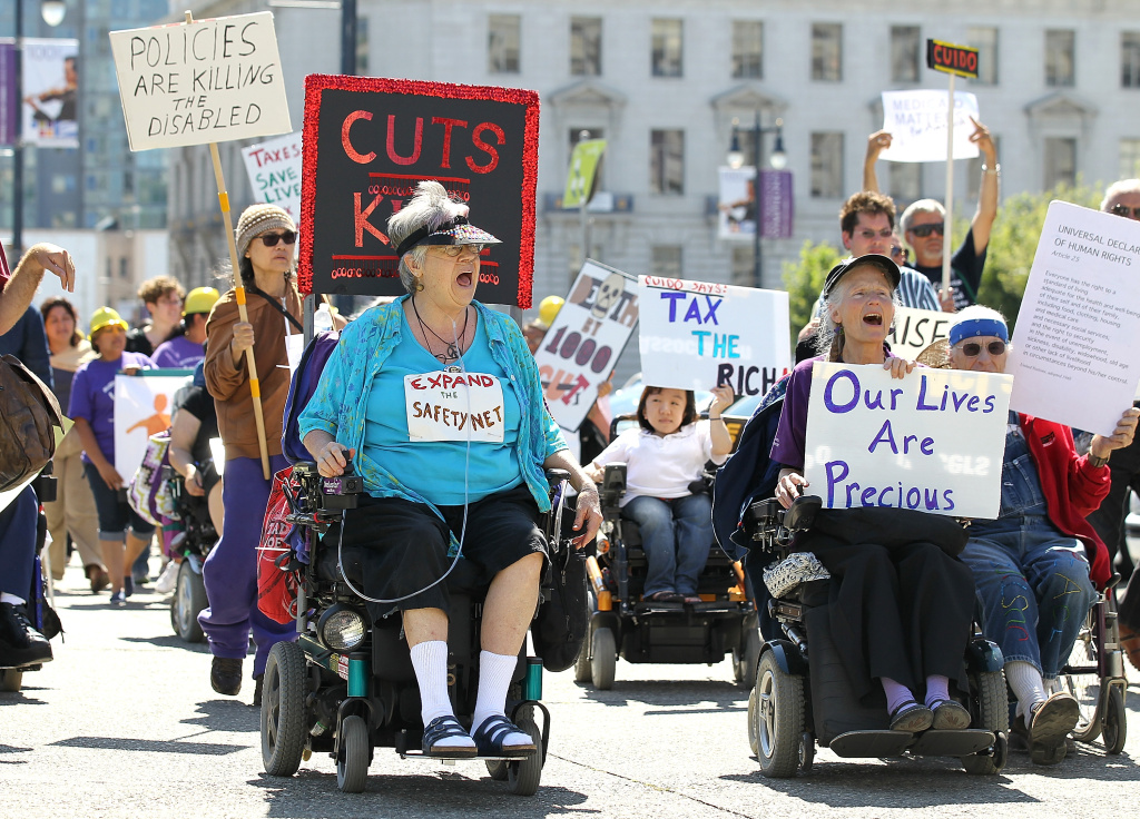 SAN FRANCISCO, CA - SEPTEMBER 21: Disabled people carry signs as they protest cuts to Medical and Medicare on September 21, 2011 in San Francisco, California.