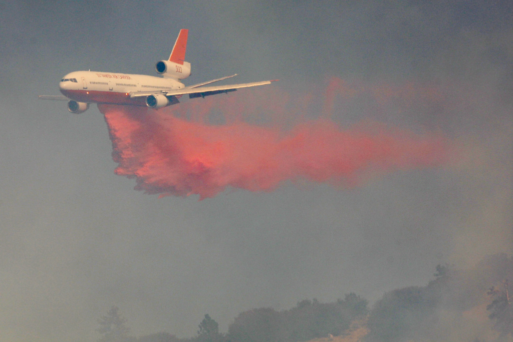 A 10 Tanker, DC-10 firefighting jet, flies through a smoky sky while dropping Phos-Check fire retardant as firefighters try to prevent the 3,500-acre Sheep fire from reaching the mountain town of Wrightwood, a half-mile away, in 2009 near Wrightwood, California.