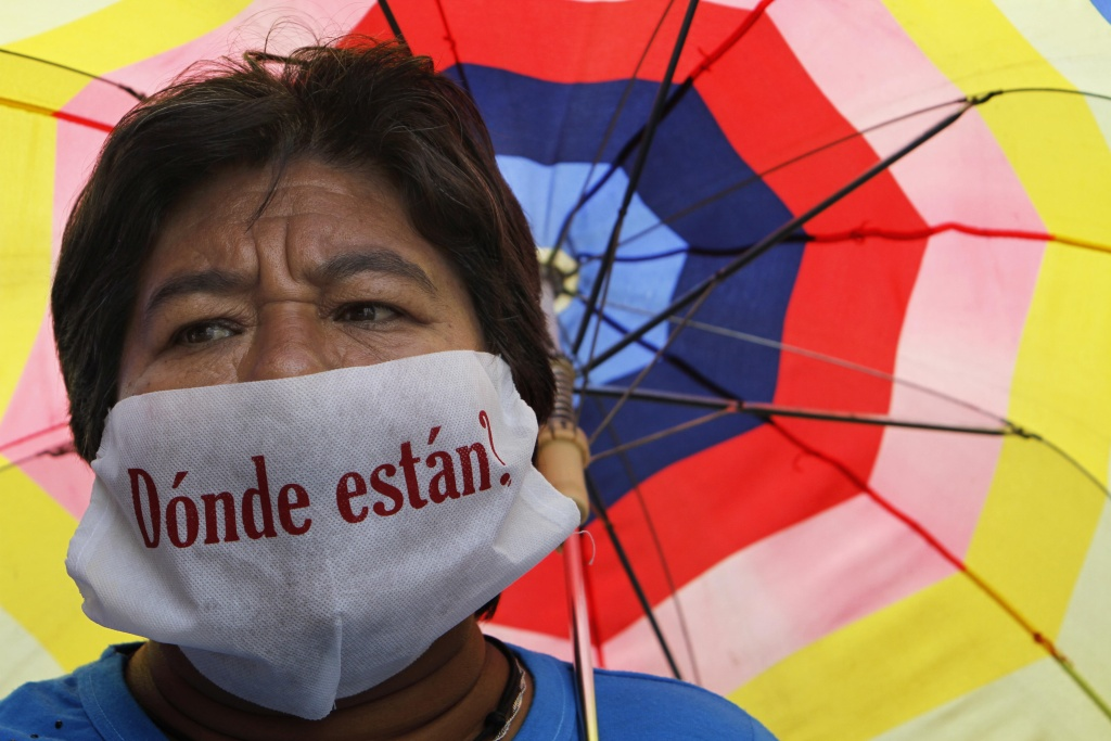 An unidentified mother, whose son is missing, wears a mask over her mouth with a message that reads in Spanish;