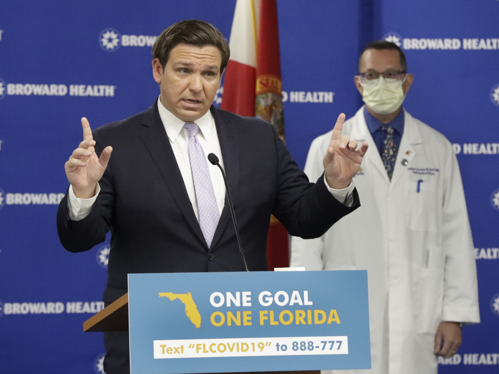 Florida Gov. Ron DeSantis, left, speaks during a news conference along with Dr. Joshua Lenchus, chief medical officer of Broward Health Medical Center on Monday. The number of patients in Florida hospitals for COVID-19 was relatively stable, at just below 8,000 and down from highs above 9,500 nearly two weeks ago.