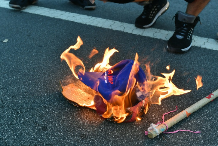 A woman burns an American flag during a protest near where Republican presidential candidate Donald Trump held a rally in San Jose, California on June 2, 2016.