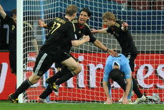 Germany's midfielder Sami Khedira (2nd left) celebrates his goal with teammates defender Per Mertesacker (L) and striker Stefan Kiessling (rear) while Uruguay's defender Diego Godin falls during the World Cup third-place soccer match between Germany and Uruguay at Nelson Mandela Bay Stadium in Port Elizabeth, South Africa on Saturday. Germany won 3-2.