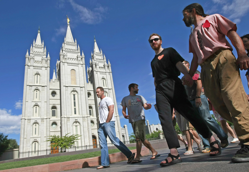 Lionel Trepanier (R) and Lucas Paul (2nd-R) walk past the Mormon Temple on the Main Street Plaza holding hands with other protesters July 12, 2009 in Salt Lake City, Utah. The protesters defied church security warnings and walked onto the plaza anyway to protest the detention and handcuffing of two gay men for holding hands and one kissing the other on the cheek there on July 9, 2009.