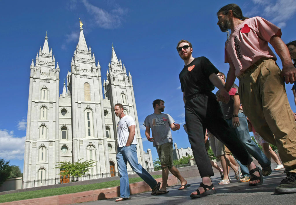 Lionel Trepanier (R) and Lucas Paul (2nd-R) walk past the Mormon Temple on the Main Street Plaza holding hands with other protesters July 12, 2009 in Salt Lake City, Utah. The protesters defied church security warnings and walked onto the plaza anyway to protest the detention and handcuffing of two gay men for holding hands and one kissing the other on the cheek there on July 9. The men were also sited by the Salt Lake City police.