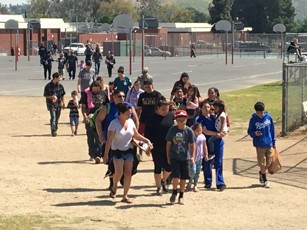 Reunited families emerged from Cajon High School Monday afternoon following a shooting at North Park Elementary School in San Bernardino that left two adults dead and two students injured.