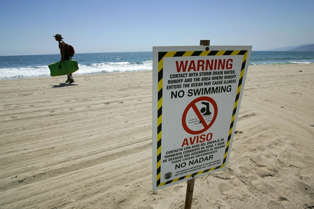 Signs warn the public to stay out of the water in an area harboring high bacteria levels near a drain at Will Rogers State Beach in August 2007 in Pacific Palisades.