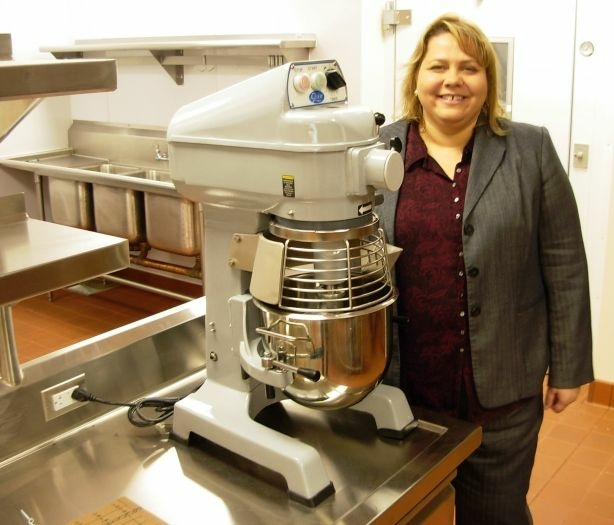 Downtown Women's Center CEO Lisa Watson witha new commercial mixer, donated by the Rotary Club, in the DWC's huge new facility, which includes a giant new kitchen, which doubles as job training center for the women who rely on the center for a dignified life.