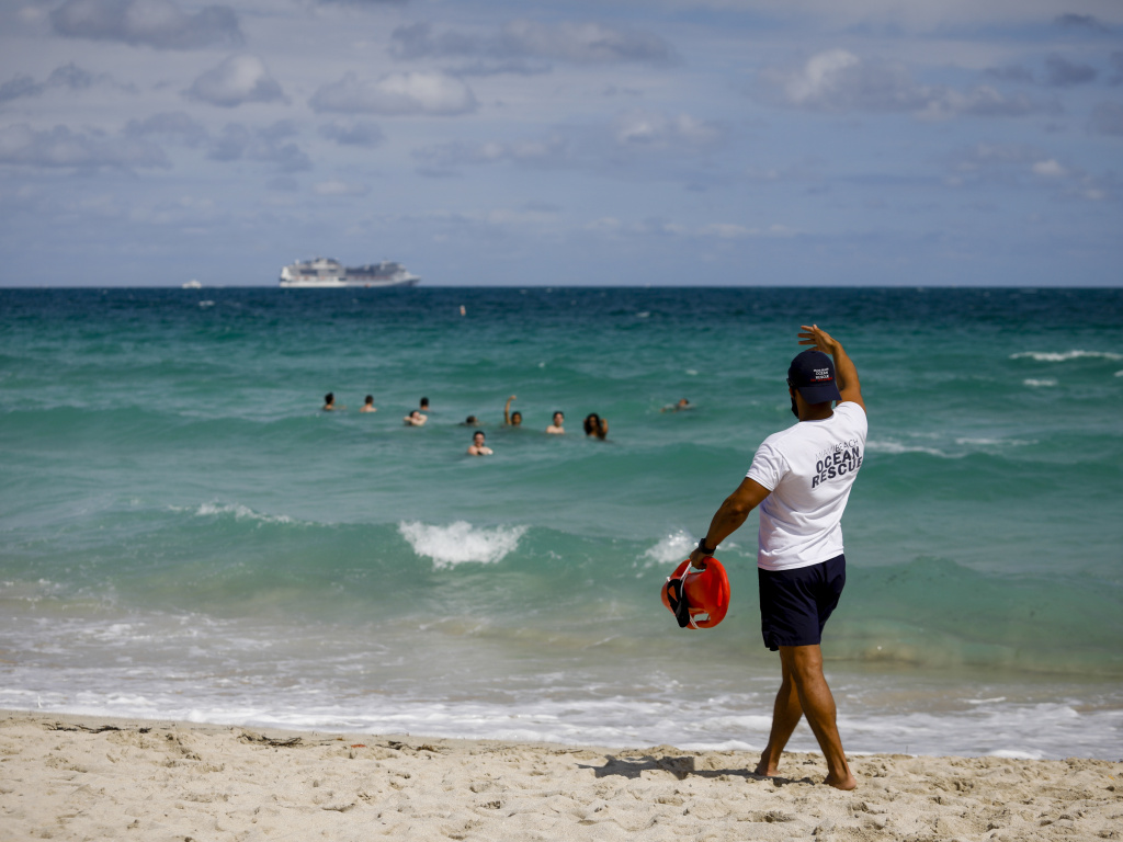A life guard calls to swimmers at a beach in Miami on March 5, 2021. Amid fears of fueling a new surge in virus cases, the city of Miami Beach on Saturday announced an abrupt curfew to curb swelling crowds of spring breakers.