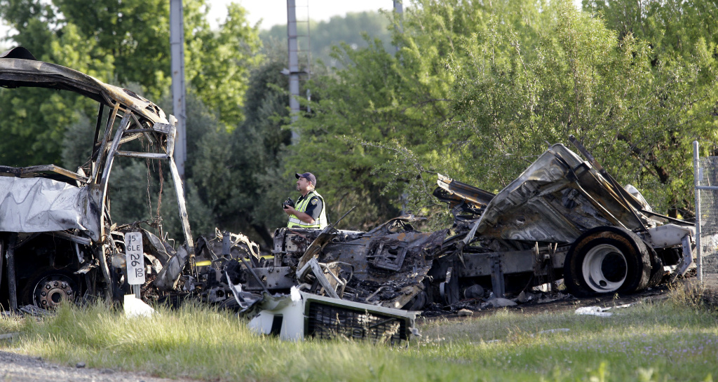 A California Highway Patrol Officer looks over  the wreckage, Friday, April 11, 2014, where a tour bus and a FedEX truck crashed on Interstate 5 Thursday in Orland, Calif.