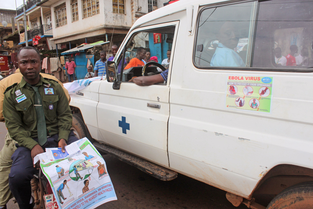 In this photo taken on Monday, Aug. 4, 2014,  health workers, left, traveling by motorbike with others inside a truck, right, as they attempt to educate people about the deadly Ebola virus in the city of  Freetown, Sierra Leone. The global Ebola outbreak touched American shores more definitively Monday, as Atlanta awaited the arrival of its second Ebola patient by morning, and a New York hospital announced it had isolated a man with possible symptoms who walked into its emergency room.(AP Photo/ Youssouf Bah)
