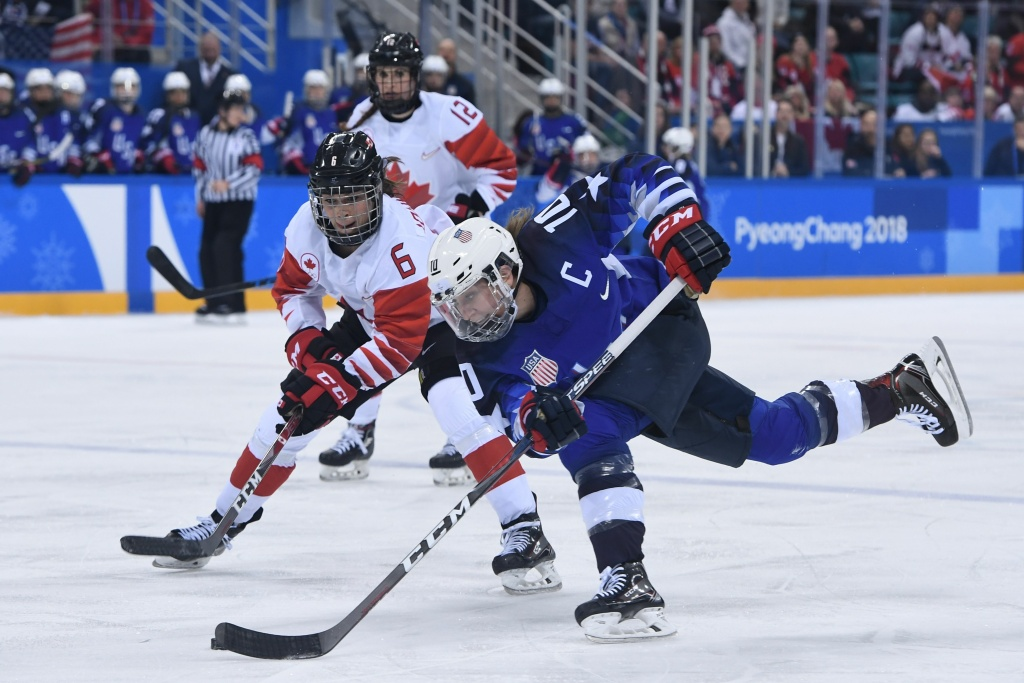 USA's Meghan Duggan (front) controls the puck in front of Canada's Rebecca Johnston in overtime in the women's gold medal ice hockey match between the US and Canada during the Pyeongchang 2018 Winter Olympic Games on February 22, 2018.