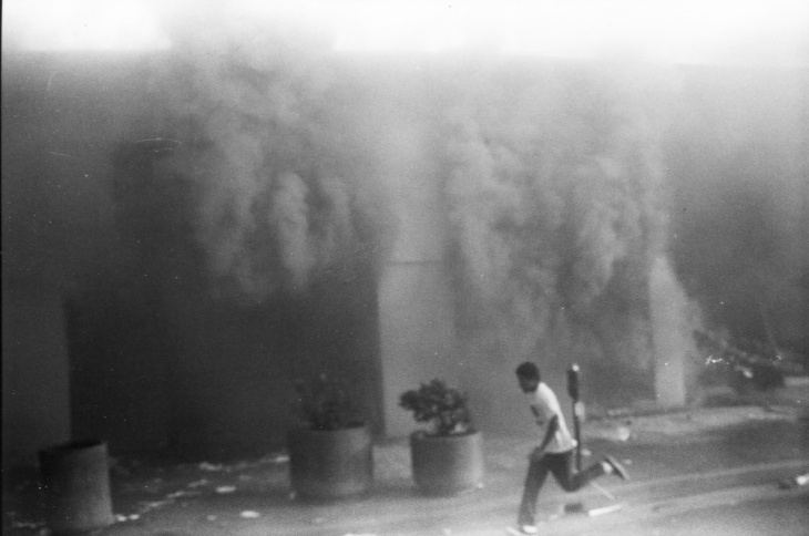 One of a series of photographs taken by photographer Gary Leonard and his then fourteen-year-old son, David Leonard, during the Los Angeles Riots, 1992.
