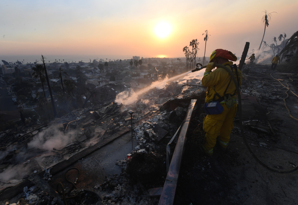 A firefighter hoses down flareups at the two story Hawaiian Village Apartment complex that burnt to the ground during the Thomas wildfire in Ventura on Dec. 5, 2017.